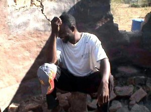 A man in Gokwe sits in the ruins of his house destroyed by youth militia  and war vets in May 2008.